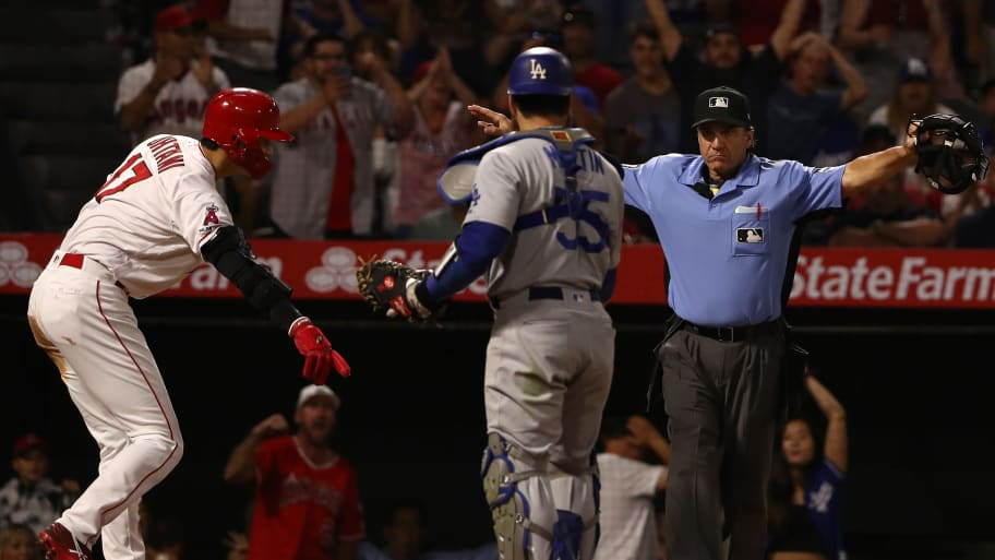 ANAHEIM, CALIFORNIA - JUNE 10: Homeplate umpire Phil Cuzzi calls Shohei Ohtani #17 of the Los Angeles Angels safe at home as catcher Russell Martin #55 of the Los Angeles Dodgers looks on in the eighth inning of the MLB game at Angel Stadium of Anaheim on June 10, 2019 in Anaheim, California. (Photo by Victor Decolongon/Getty Images)