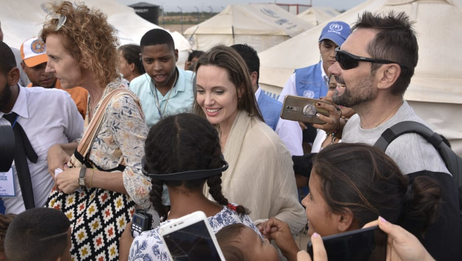 MAICAO, COLOMBIA - JUNE 08: United Nations High Commissioner for Refugees (UNCHR) Special Envoy Angelina Jolie greets children during her visit to a refugee camp in the border between Colombia and Venezuela on June 8, 2019 in Maicao, Colombia. UN and International Organization for Migration (IOM) announced yesterday that 4 million of Venezuelans have left their country since 2015 due to the social, political and economic crisis, which means they are of the single largest population groups displaced from their country globally. The camp in Maicao has 60 tents  which can accommodate up to 350 people. Due to high demand, UNHCR is considering an expansion to give shelter to 1,400 people. Colombia it the top host of Venezuelan migrants and refugees, accounting 1.3 million. (Photo by Guillermo Legaria/Getty Images)
