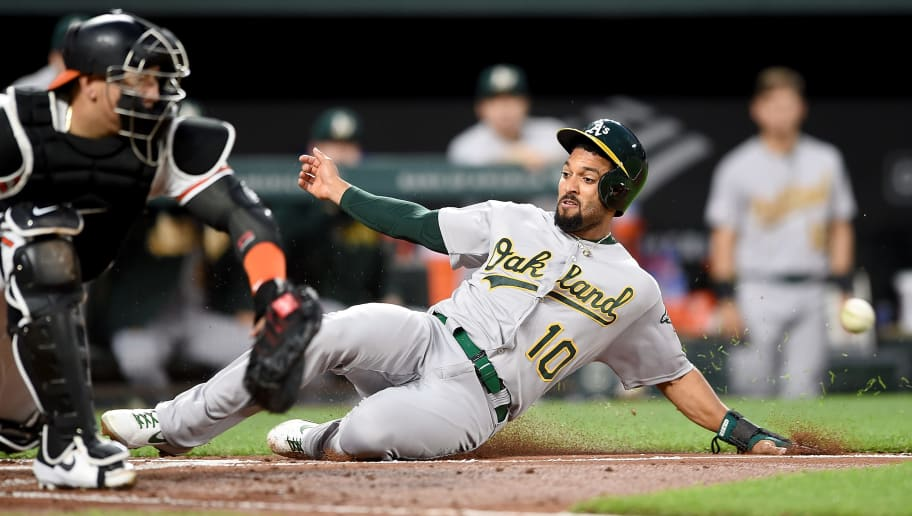 BALTIMORE, MD - APRIL 10:  Marcus Semien #10 of the Oakland Athletics scores ahead of the throw to Jesus Sucre #40 of the Baltimore Orioles in the third inning at Oriole Park at Camden Yards on April 10, 2019 in Baltimore, Maryland.  (Photo by Greg Fiume/Getty Images)