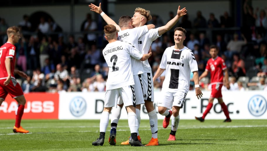 BERLIN, GERMANY - MAY 19:  Carlo Boukhalfa (L) of Freiburg celebrates with his teammates after scoring his teams second goal during the DFB Juniors Cup Final 2018 between 1. FC Kaiserslautern U19 and SC Freiburg U19 at Stadion am Wurfplatz on May 19, 2018 in Berlin, Germany.  (Photo by Lars Baron/Bongarts/Getty Images)