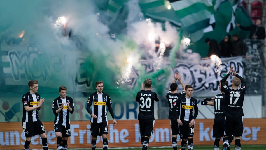 MAINZ, GERMANY - APRIL 01: Team mates  of Moenchengladbachreact as their supporters light fireworks during the Bundesliga match between 1. FSV Mainz 05 and Borussia Moenchengladbach at Opel Arena on April 1, 2018 in Mainz, Germany. (Photo by Simon Hofmann/Bongarts/Getty Images)