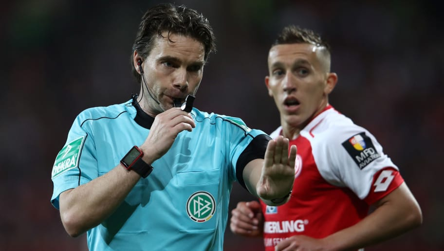 MAINZ, GERMANY - APRIL 16:  Referee Guido Winkmann gestures as goal scorer Pablo de Blasis of Mainz looks on during the Bundesliga match between 1. FSV Mainz 05 and Sport-Club Freiburg at Opel Arena on April 16, 2018 in Mainz, Germany.  (Photo by Alex Grimm/Bongarts/Getty Images)