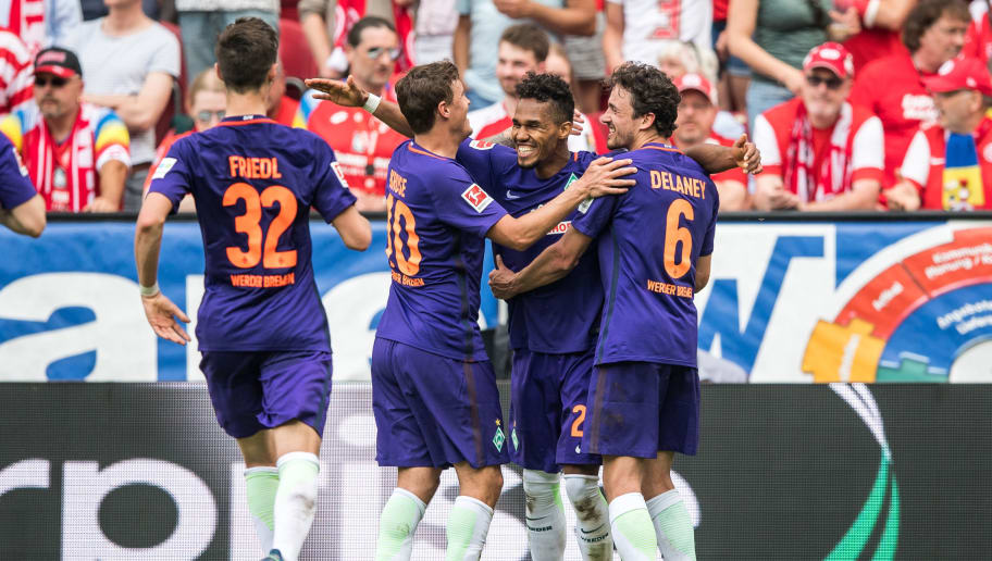MAINZ, GERMANY - MAY 12: Scorer  Theodor Gebre Selassie (2R) celebrates his teams second goal with Marco Friedl (L), Max Kruse (2L) and Thomas Delaney during the Bundesliga match between 1. FSV Mainz 05 and SV Werder Bremen at Opel Arena on May 12, 2018 in Mainz, Germany. (Photo by Lukas Schulze/Bongarts/Getty Images)