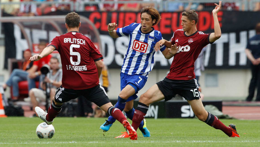 NUREMBERG, GERMANY - AUGUST 18:  Niklas Stark (R) and Hanno Balisch (L) of Nuernberg fights for the ball with Hajime Hosogai of Berlin during the Bundesliga match between 1. FC Nuernberg and Hertha BSC Berlin at Grundig Stadium on August 18, 2013 in Nuremberg, Germany.  (Photo by Boris Streubel/Getty Images)