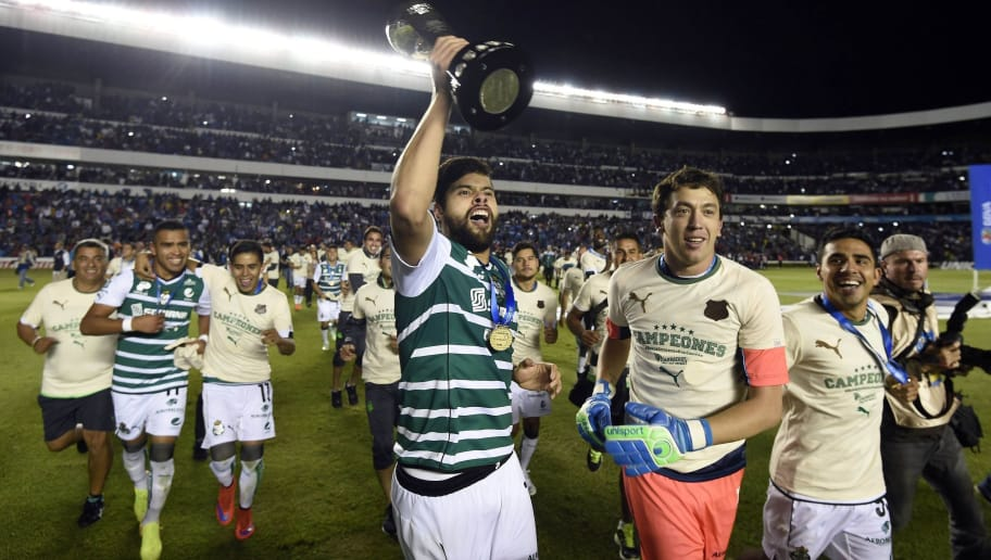 Nestor Araujo (L) and Agustin Marchesin (R) of Santos hold their trophy after winning against Queretaro in during their final match of Mexican Clasura 2015 tournament in Queretaro, Mexico, on May 31, 2015. AFP PHOTO/ALFREDO ESTRELLA        (Photo credit should read ALFREDO ESTRELLA/AFP/Getty Images)