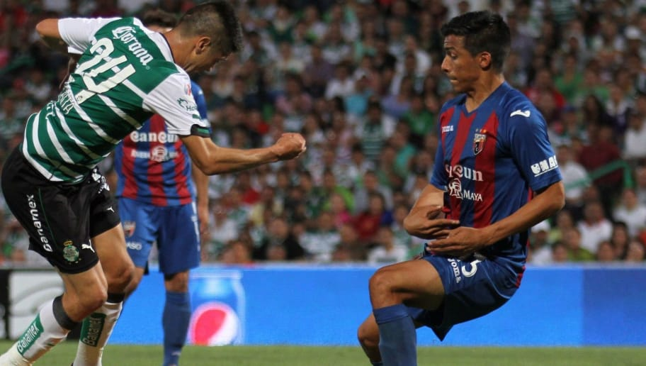Oribe Peralta (L) of Santos vies for the ball with Angel Sepulveda (R) of Atlante, during their Mexican Clausura tournament football match on April 13, 2014 in Torreón, Mexico. AFP PHOTO/SIMÓN CORRAL        (Photo credit should read Simon CORRAL/AFP/Getty Images)