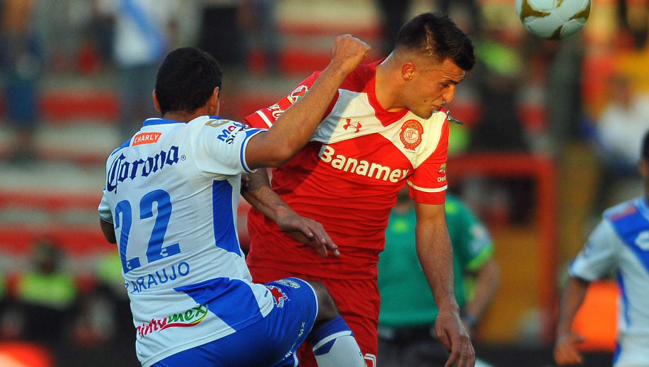 Enrique Triverio (R) of Toluca vies for the ball with Patricio Araujo of Puebla during their Mexican Apertura football tournament quarterfinal match at the Nemesio Diez stadium in Toluca, Mexico, on November 29, 2015. AFP PHOTO/MARIA CALLS / AFP / MARIA CALLS        (Photo credit should read MARIA CALLS/AFP/Getty Images)