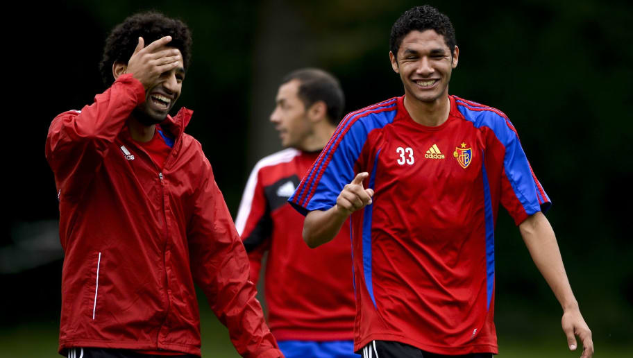 FC Basel's Egyptian midfielder Mohamed Salah (L) shares a light moment with compatriot midfielder Mohamed Elneny (R) during a training session on September 30, 2013 in Basel, on the eve of an UEFA Champions League group E football match against FC Schalke 04. AFP PHOTO / FABRICE COFFRINI        (Photo credit should read FABRICE COFFRINI/AFP/Getty Images)