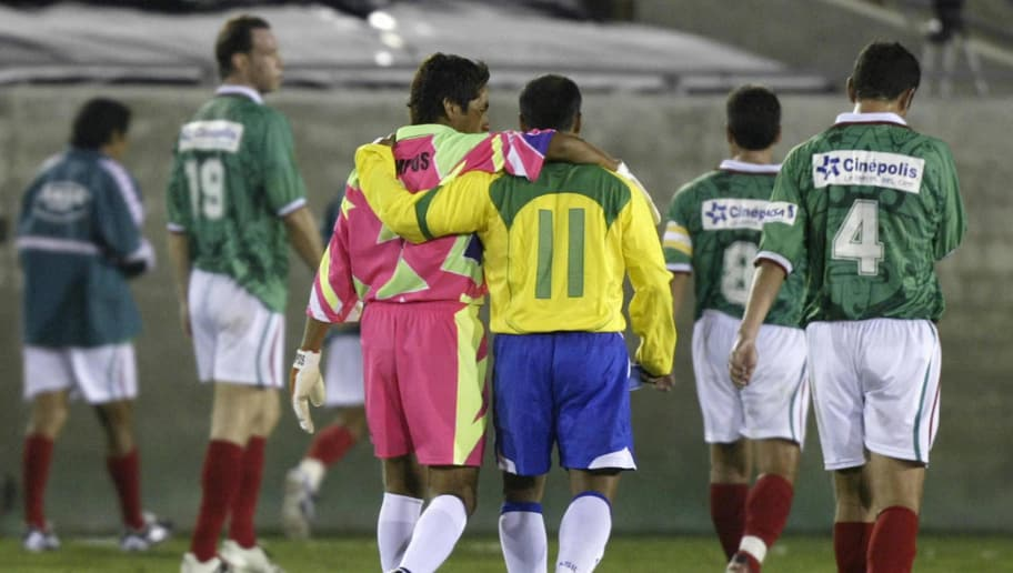 LOS ANGELES, UNITED STATES:  Brazilian soccer star Romario de Souza Faria (R) and Mexican goalkeepr Jorge Campos (L) walk off the pitch together at the end of the first half of  'La Gran Despedida', 'The Grand Farewell', a match between Mexico and Brazil to mark the international retirement of Romario and Campos, 10 November 2004 at the Los Angeles Coliseum.  AFP PHOTO / Robyn BECK  (Photo credit should read ROBYN BECK/AFP/Getty Images)