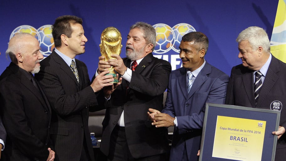 Brazilian president Luiz Inacio Lula da Silva (C) holds the FIFA World Cup trophy with (From L) Brazilian author Paulo Coelho, coach of the Brazilian football team, Dunga, former legendary player Romario and president of the Brazilian Football Federation (CFB) Ricardo Teixeira after the official unveil of Brazil as the 2014 World Cup hosts country, 30 October 2007 at the World football's governing body headquarters in Zurich. FIFA President Sepp Blatter announced Brazil as the venue after the sole candidate's final presentation to FIFA's executive committee. AFP PHOTO / FABRICE COFFRINI (Photo credit should read FABRICE COFFRINI/AFP/Getty Images)