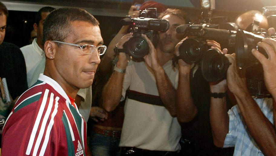 Brazilian soccer star Romario wearing his new club Fluminense shirt, is surrounded by the media upon his arrival at Rio de Janeiro's international airport, 09 June, 2003. Romario, who played for Quatar's El-Saad team during three months for a 1,5 million dollars salary, returned this Monday to Rio de Janeiro to participate at the Brazilian tournement defending his new team colours.    AFP PHOTO/VANDERLEI ALMEIDA  (Photo credit should read VANDERLEI ALMEIDA/AFP/Getty Images)