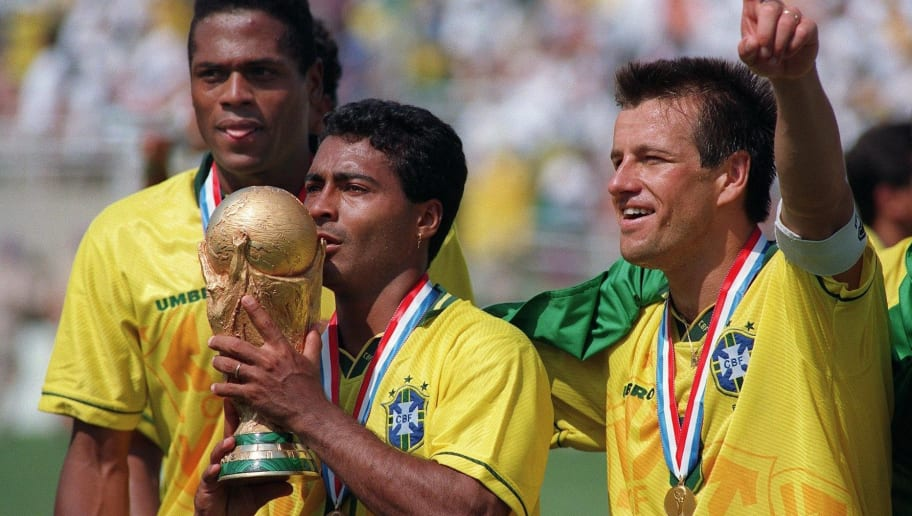 Brazilian forward Romario kisses the FIFA World Cup trophy, flanked by Ronaldao (L) and captain Dunga, after Brazil defeated Italy 3-2 in the shoot-out session (0-0 after extra time) at the end of the World Cup final, 17 July 1994 at the Rose Bowl in Pasadena. Italian Roberto Baggio missed his penalty kick to give Brazil its fourth World Cup title after 1958, 1962 and 1970.    AFP PHOTO/DANIEL GARCIA        (Photo credit should read DANIEL GARCIA/AFP/Getty Images)