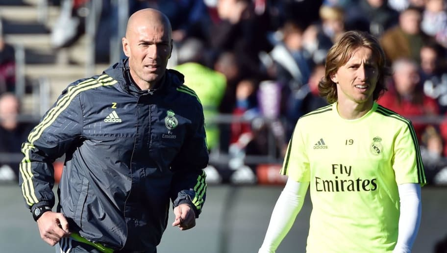 Real Madrid's new French coach Zinedine Zidane (C) runs past Real Madrid's Croatian midfielder Luka Modric (R) during his first training session as coach of Real Madrid at the Alfredo di Stefano stadium in Valdebebas, on the outskirts of Madrid, on January 5, 2016. Real Madrid legend Zinedine Zidane promised to put his 'heart and soul' into managing the Spanish giants after he was sensationally named as coach following Rafael Benitez's unceremonious sacking. AFP PHOTO/ GERARD JULIEN / AFP / GERARD JULIEN        (Photo credit should read GERARD JULIEN/AFP/Getty Images)