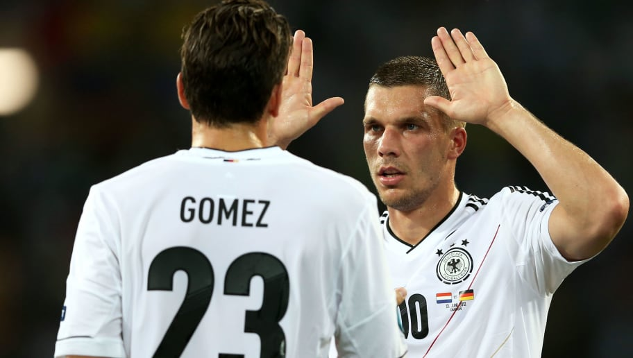 KHARKOV, UKRAINE - JUNE 13:  Mario Gomez of Germany celebrates scoring the opening goal with Lukas Podolski of Germany during the UEFA EURO 2012 group B match between Netherlands and Germany at Metalist Stadium on June 13, 2012 in Kharkov, Ukraine.  (Photo by Julian Finney/Getty Images)