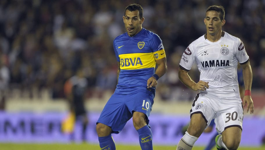 Boca Juniors forward Carlos Tevez (L) receives the ball marked by Lanus midfielder Ivan Marcone during their Argentina First Division football match against Lanus at the Nestor Diaz Perez stadium in Lanus, Buenos Aires, on March 20, 2016. AFP PHOTO / ALEJANDRO PAGNI / AFP / ALEJANDRO PAGNI        (Photo credit should read ALEJANDRO PAGNI/AFP/Getty Images)