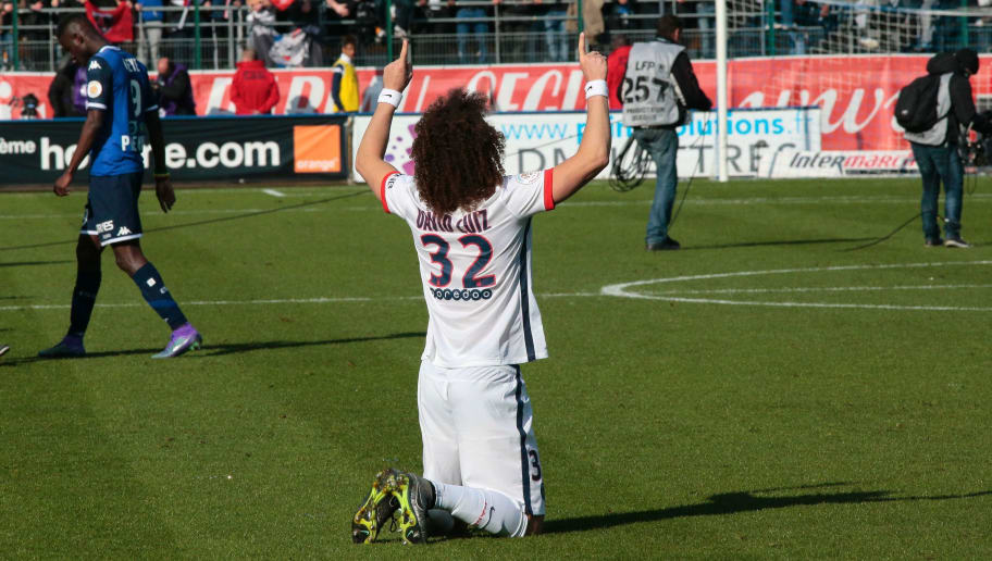 Paris Saint-Germain's Brazilian defender David Luiz (C) prays as he celebrates after winning the French Ligue 1 football match against Troyes on March 13, 2016 at the Aube Stadium in Troyes. Paris Saint-Germain clinched a fourth consecutive Ligue 1 title in record time on March 13 after defeating Troyes, obliterating a new French record for the quickest league victory with eight games to spare before the end of the L1 championships. / AFP / JACQUES DEMARTHON        (Photo credit should read JACQUES DEMARTHON/AFP/Getty Images)