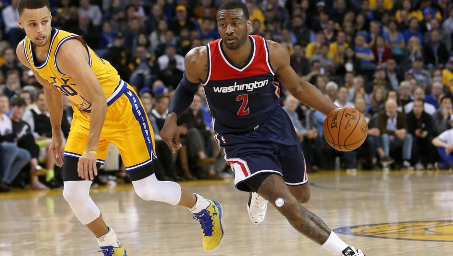 OAKLAND, CA - MARCH 29:  John Wall #2 of the Washington Wizards drives on Stephen Curry #30 of the Golden State Warriors at ORACLE Arena on March 29, 2016 in Oakland, California. NOTE TO USER: User expressly acknowledges and agrees that, by downloading and or using this photograph, User is consenting to the terms and conditions of the Getty Images License Agreement.  (Photo by Ezra Shaw/Getty Images)