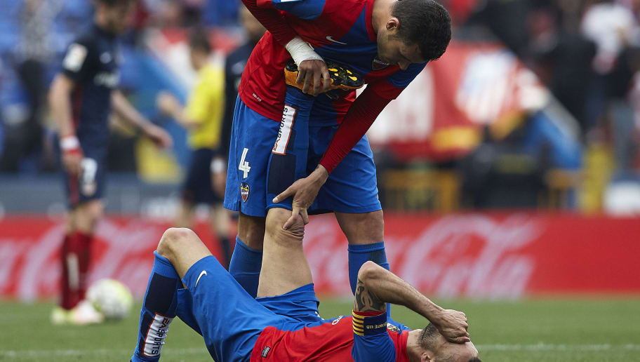 VALENCIA, SPAIN - MAY 08:  David Navarro of Levante help the injured his teammate Juanfran during La Liga match between Levante UD and Atletico de Madrid at Ciutat de Valencia on May 8, 2016 in Valencia, Spain.  (Photo by Manuel Queimadelos Alonso/Getty Images)