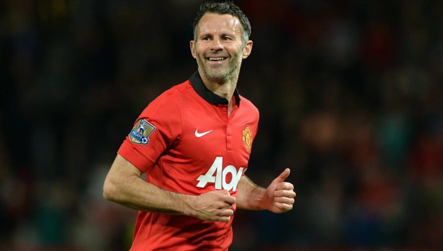 Manchester United's Interim Welsh player-manager Ryan Giggs smiles after taking a free kick during the English Premier League football match between Manchester United and Hull City at Old Trafford in Manchester, northwest England on May 6, 2014. Manchester United interim manager Ryan Giggs named himself on the bench for his side's home game with Hull City on Tuesday, potentially setting the scene for a farewell appearance. Giggs, 40, will step down as interim manager after Sunday's final Premier League game at Southampton and his contract as a player is also due to expire. Manchester United won the game 3-1. AFP PHOTO / PAUL ELLIS  RESTRICTED TO EDITORIAL USE. No use with unauthorized audio, video, data, fixture lists, club/league logos or live services. Online in-match use limited to 45 images, no video emulation. No use in betting, games or single club/league/player publications.        (Photo credit should read PAUL ELLIS/AFP/Getty Images)