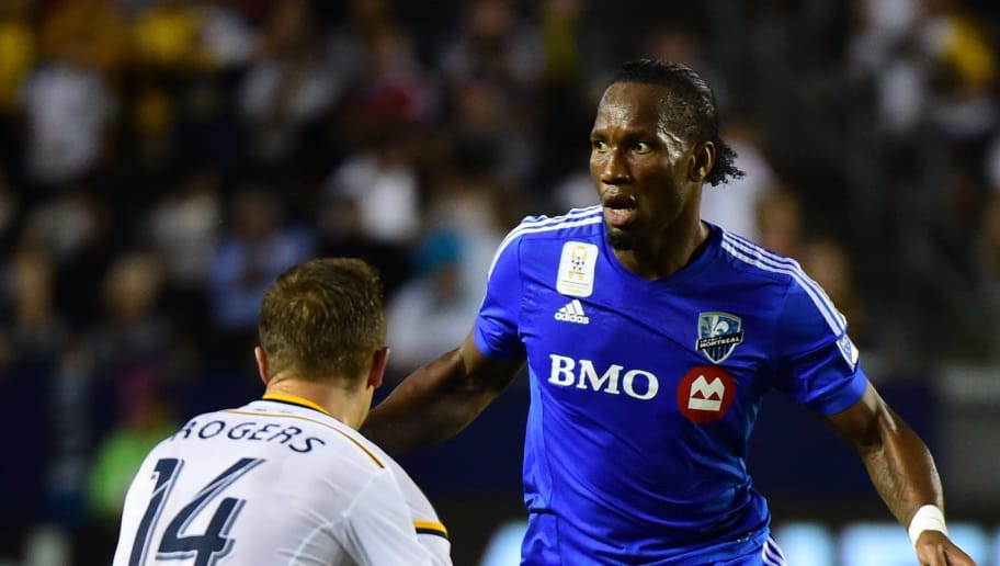Didier Drogba of the Montreal Impact looks to pass under pressure from Robbie Rogers of the LA Galaxy in their MLS match on September 12, 2015 in Carson, California which ended 0-0. AFP PHOTO /FREDERIC J.BROWN        (Photo credit should read FREDERIC J. BROWN/AFP/Getty Images)