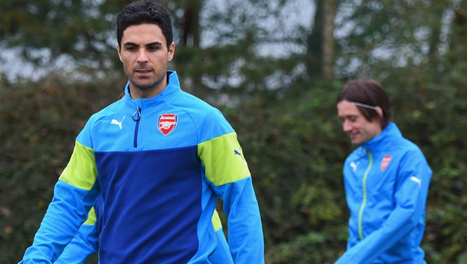 ST ALBANS, ENGLAND - NOVEMBER 03:  (L-R) Serge Gnabry, Mikel Arteta and Tomas Rosicky look on during an Arsenal training session ahead of the UEFA Champions League match against RSC Anderlecht at London Colney on November 3, 2014 in St Albans, England.  (Photo by Michael Regan/Getty Images)
