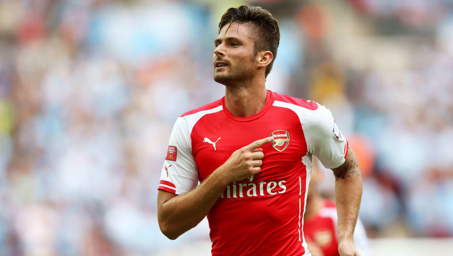 LONDON, ENGLAND - AUGUST 10: Olivier Giroud of Arsenal points to the badge on his shirt as he celebrates scoring the third goal during the FA Community Shield match between Manchester City and Arsenal at Wembley Stadium on August 10, 2014 in London, England.  (Photo by David Rogers/Getty Images)