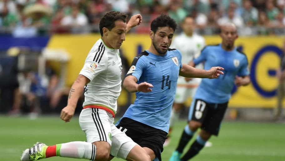 Mexico's Andres Guardado (L) is marked by Uruguay's Nicolas Lodeiro during the Copa America Centenario football tournament in Glendale, Arizona, United States, on June 5, 2016.  / AFP / NELSON ALMEIDA        (Photo credit should read NELSON ALMEIDA/AFP/Getty Images)
