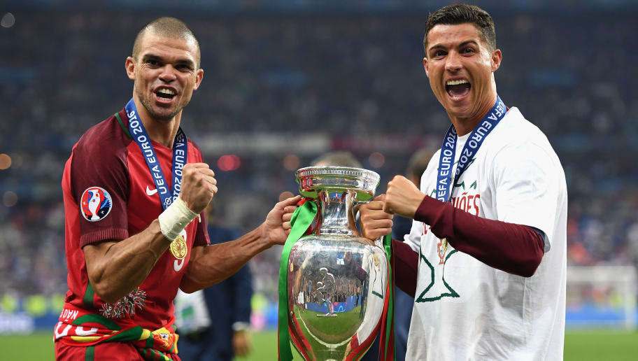 PARIS, FRANCE - JULY 10:  Cristiano Ronaldo (R) and Pepe (L) of Portugal pose for photographs holding the Henri Delaunay trophy to celebrate after their 1-0 win against France in the UEFA EURO 2016 Final match between Portugal and France at Stade de France on July 10, 2016 in Paris, France.  (Photo by Laurence Griffiths/Getty Images)
