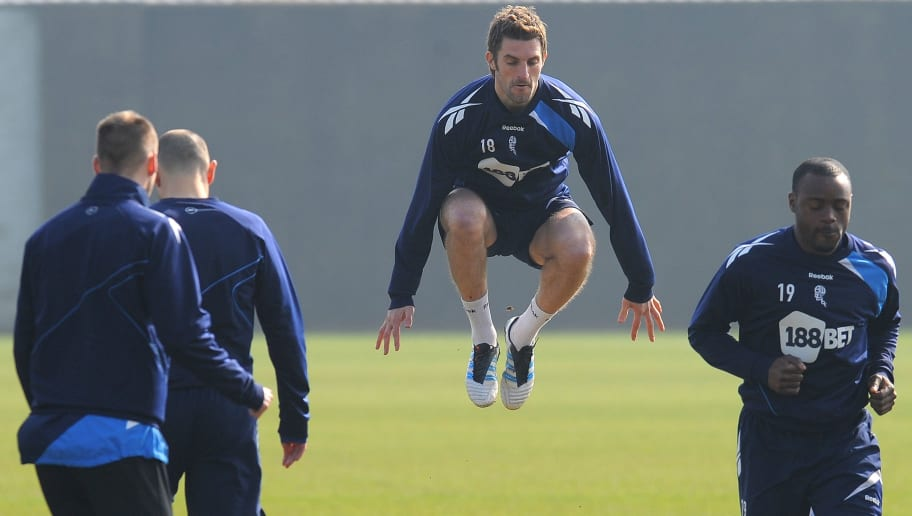 "Bolton Wanderers' Welsh defender Sam Ricketts (C) jumps a hurdle during a training session at their Euxton training ground near Bolton, north-west England, on March 22 2012. Bolton manager Owen Coyle admits his players will find it hard to put Fabrice Muamba out of their minds when they return to action for the first time since the midfielder's harrowing collapse.  AFP PHOTO / ANDREW YATES   RESTRICTED TO EDITORIAL USE. No use with unauthorized audio, video, data, fixture lists, club/league logos or ""live"" services. Online in-match use limited to 45 images, no video emulation. No use in betting, games or single club/league/player publications. (Photo credit should read ANDREW YATES/AFP/Getty Images)"