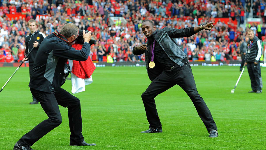 "Manchester United supporter, Jamaican Olympic sprint champion Usain Bolt recreates his famous celebration on the pitch while showing off his gold medals before the English Premier League football match between Manchester United and Fulham at Old Trafford in Manchester, north-west England on August 25, 2012. AFP PHOTO/ANDREW YATES  RESTRICTED TO EDITORIAL USE. No use with unauthorized audio, video, data, fixture lists, club/league logos or ""live"" services. Online in-match use limited to 45 images, no video emulation. No use in betting, games or single club/league/player publications        (Photo credit should read ANDREW YATES/AFP/GettyImages)"