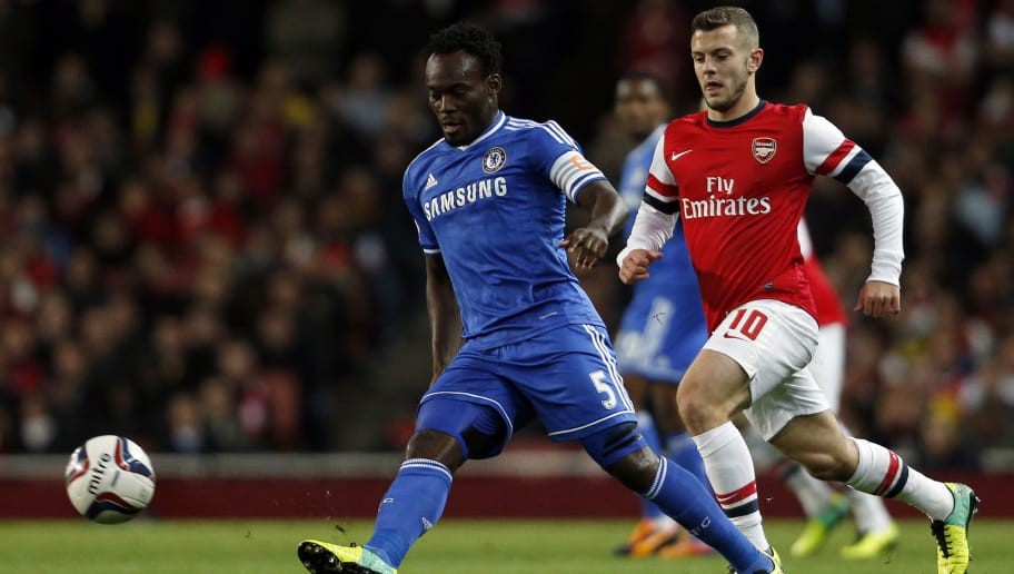 Chelsea's Ghanian midfielder Michael Essien (L) plays the ball as Arsenal's English midfielder Jack Wilshere (R) chases during the English League Cup fourth round football match between Arsenal and Chelsea at the Emirates Stadium in London on October 29, 2013. AFP PHOTO / ADRIAN DENNIS  RESTRICTED TO EDITORIAL USE. No use with unauthorized audio, video, data, fixture lists, club/league logos or live services. Online in-match use limited to 45 images, no video emulation. No use in betting, games or single club/league/player publications.        (Photo credit should read ADRIAN DENNIS/AFP/Getty Images)