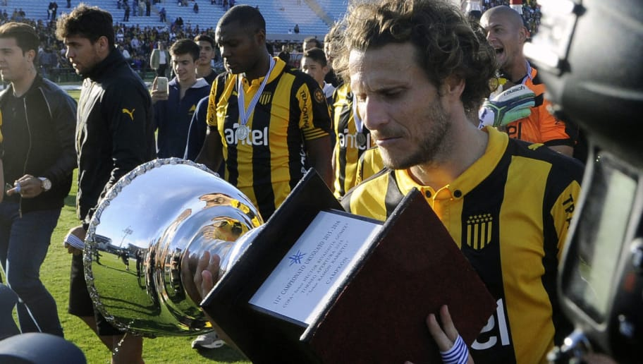 Uruguayan footballer Diego Forlan holds the trophy after Penarol defeated Juventud 1-0 to win the Apertura football tournament, at the Centenario stadium in Montevideo, on December 6, 2015.  AFP PHOTO / MIGUEL ROJO / AFP / MIGUEL ROJO        (Photo credit should read MIGUEL ROJO/AFP/Getty Images)