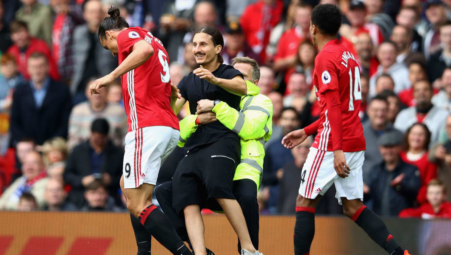 MANCHESTER, ENGLAND - SEPTEMBER 24: A Manchester United fan invades the pitch and attempts to reach Zlatan Ibrahimovic of Manchester United but is stopped by stewards  during the Premier League match between Manchester United and Leicester City at Old Trafford on September 24, 2016 in Manchester, England.  (Photo by Clive Brunskill/Getty Images)