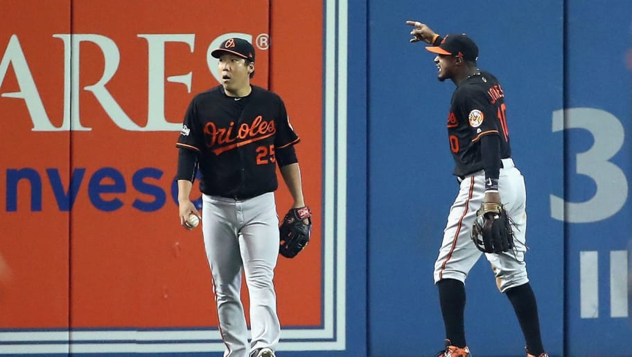 TORONTO, ON - OCTOBER 04:  Hyun Soo Kim #25 of the Baltimore Orioles and Adam Jones #10 react in the seventh inning after a fan threw a beverage onto the field during the American League Wild Card game against the Toronto Blue Jays at Rogers Centre on October 4, 2016 in Toronto, Canada.  (Photo by Tom Szczerbowski/Getty Images)