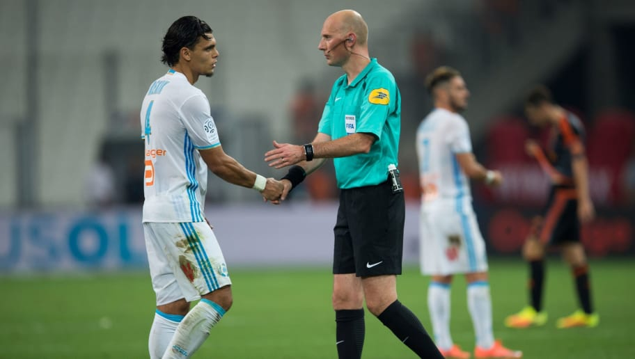 French referee Antony Gautier (R) shakes hands with Olympique de Marseille's Dutch defender Karim Rekik (L) during the French Ligue 1 football match Olympique de Marseille versus Lorient on August 26, 2016 at the Velodrome stadium in Marseille, southern France. / AFP / BERTRAND LANGLOIS        (Photo credit should read BERTRAND LANGLOIS/AFP/Getty Images)