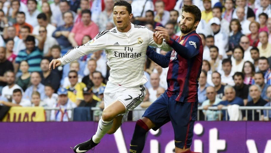 Real Madrid's Portuguese forward Cristiano Ronaldo (L) vies with Barcelona's defender Gerard Pique during the Spanish league 'Clasico' football match Real Madrid CF vs FC Barcelona at the Santiago Bernabeu stadium in Madrid on October 25, 2014.  AFP PHOTO / GERARD JULIEN        (Photo credit should read GERARD JULIEN/AFP/Getty Images)