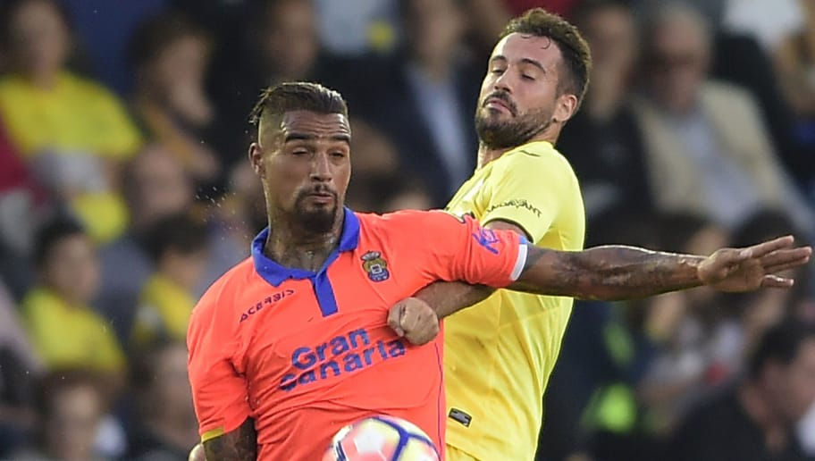CORRECTION - Las Palmas' German-Ghanaian midfielder Kevin-Prince Boateng (L) vies with Villarreal's defender Mario during the Spanish league football match between Villarreal CF and UD Las Palmas at El Madrigal stadium in Vila-real on October 23, 2016. / AFP / JOSE JORDAN / The erroneous mention[s] appearing in the metadata of this photo by JOSE JORDAN has been modified in AFP systems in the following manner: [Las Palmas' German-Ghanaian midfielder Kevin-Prince Boateng] instead of [Las Palmas' German midfielder Kevin Prince]. Please immediately remove the erroneous mention[s] from all your online services and delete it (them) from your servers. If you have been authorized by AFP to distribute it (them) to third parties, please ensure that the same actions are carried out by them. Failure to promptly comply with these instructions will entail liability on your part for any continued or post notification usage. Therefore we thank you very much for all your attention and prompt action. We are sorry for the inconvenience this notification may cause and remain at your disposal for any further information you may require.        (Photo credit should read JOSE JORDAN/AFP/Getty Images)