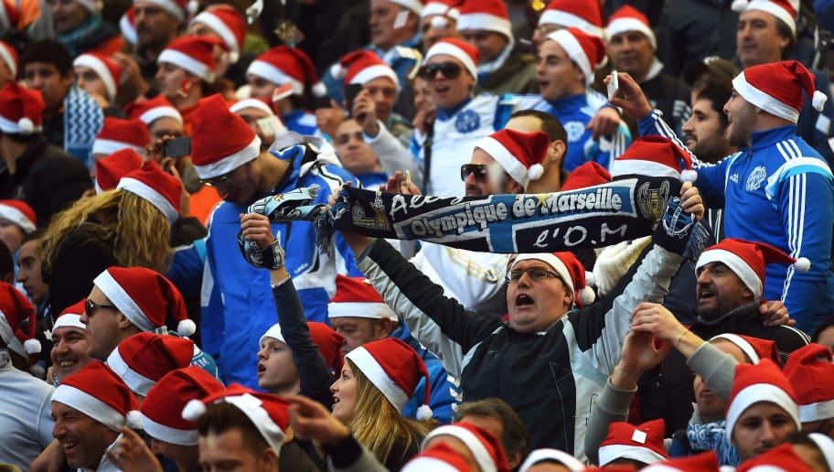 Marseille's wearing Santa Claus bonnets attend   the French L1 football match Marseille (OM) vs Lille (LOSC) on December 21, 2014 at the Velodrome stadium in Marseille, southeastern France. AFP PHOTO / ANNE-CHRISTINE POUJOULAT        (Photo credit should read ANNE-CHRISTINE POUJOULAT/AFP/Getty Images)