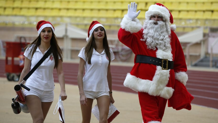 A man dressed a Santa Clause walks with two of his helpers during the French L1 football match Monaco (ASM) vs Saint Etienne (ASSE) on December 13, 2015 at the 'Louis II Stadium' in Monaco.  / AFP / VALERY HACHE        (Photo credit should read VALERY HACHE/AFP/Getty Images)