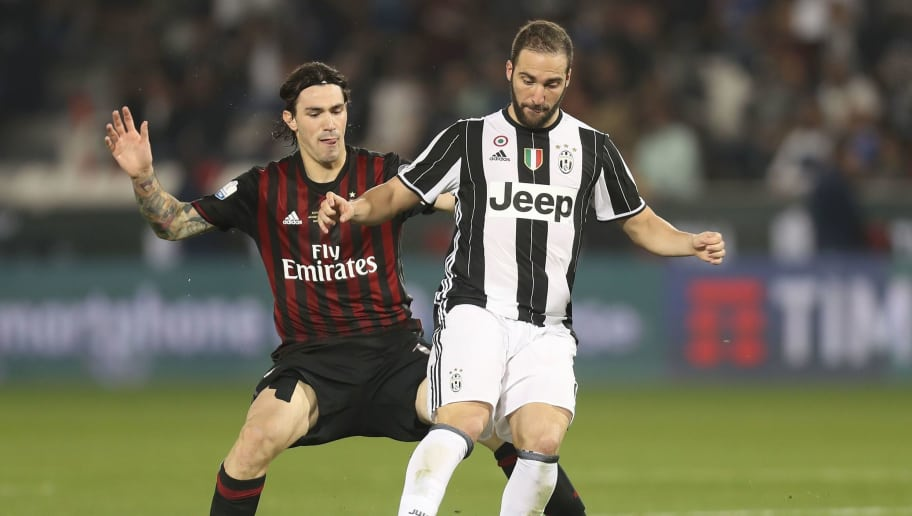 Juventus' Gonzalo Higuain (R) vies for the ball with AC Milan's player during the Italian Super Cup final match between AC Milan and Juventus in Doha on December 23, 2016. / AFP / KARIM JAAFAR (Photo credit should read KARIM JAAFAR/AFP/Getty Images)