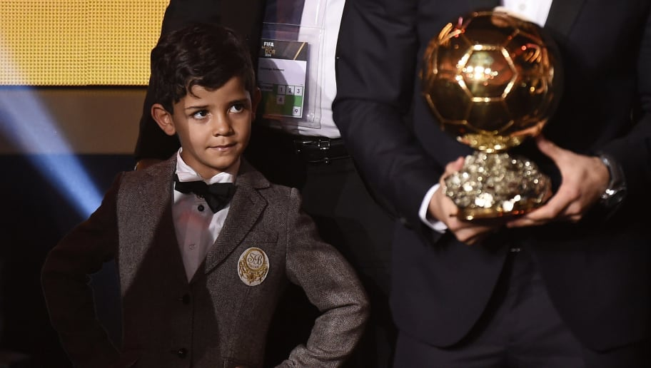 Cristiano Jr, the son of Real Madrid and Portugal forward Cristiano Ronaldo (L) looks at the trophy to his father who received the 2014 FIFA Ballon d'Or award ceremony at the Kongresshaus in Zurich on January 12, 2015. AFP PHOTO / OLIVIER MORIN        (Photo credit should read OLIVIER MORIN/AFP/Getty Images)