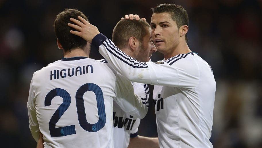 Real Madrid's French forward Karim Benzema (C) celebrates with teammates Argentinian forward Gonzalo Higuain (L) and Portuguese forward Cristiano Ronaldo after scoring during the Spanish League football match Real Madrid CF vs RCD Mallorca at the Santiago Bernabeu stadium in Madrid on March 16, 2013.  AFP PHOTO/ DANI POZO        (Photo credit should read DANI POZO/AFP/Getty Images)