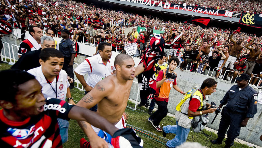 Flamengo's player Adriano (C) runs to celebrate with supporters the victory of their team in the Brazilian Championship after winning by 2-1 in their final date match against Gremio, at Maracana stadium on December 6, 2009 in Rio de Janeiro, Brazil.  AFP PHOTO / ANTONIO SCORZA (Photo credit should read ANTONIO SCORZA/AFP/Getty Images)