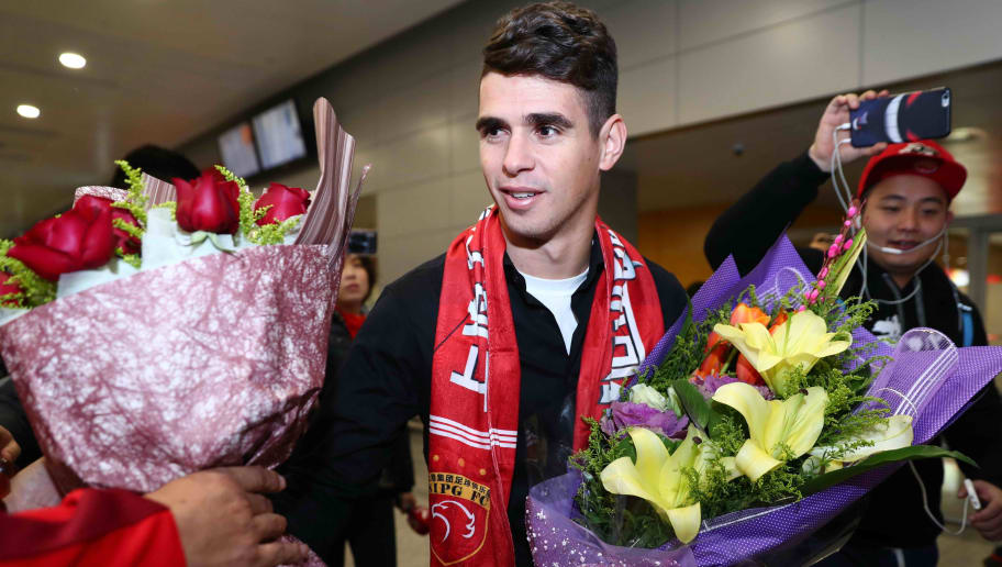 Brazilian football player Oscar (C) receives flowers as he arrives at Shanghai airport on January 2, 2017.   Brazilian midfielder Oscar landed in Shanghai on January 2, 2017 where the 25-year-old was set to smash the Asian transfer record with a reported 63 million USD deal with Shanghai SIPG. / AFP / STR / China OUT        (Photo credit should read STR/AFP/Getty Images)