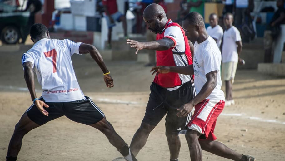 International Liberian football star, George Weah dribbles two players from the opposite team during a match played on a dusty pitch at the Alpha Old Timers Sports Association in Paynesville in Monrovia on April 30, 2016. Former international football star George Weah said on April 28, 2016, he would be a candidate in next year's presidential elections in Liberia, his second bid for the post. / AFP / MARCO LONGARI        (Photo credit should read MARCO LONGARI/AFP/Getty Images)