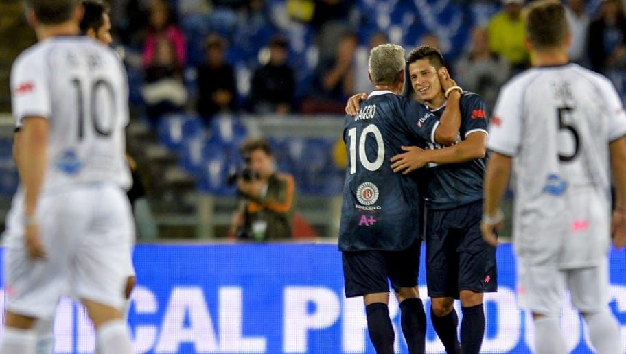 Match For Peace's Argentine forward Juan Manuel Iturbe (2 R) celebrates with his team mate Roberto Baggio after scoring against Match For Peace's opponents team during their intereligious ' Match for Peace ' football game on September 1, 2014 at Rome's Olympic stadium. AFP PHOTO / ANDREAS SOLARO        (Photo credit should read ANDREAS SOLARO/AFP/Getty Images)