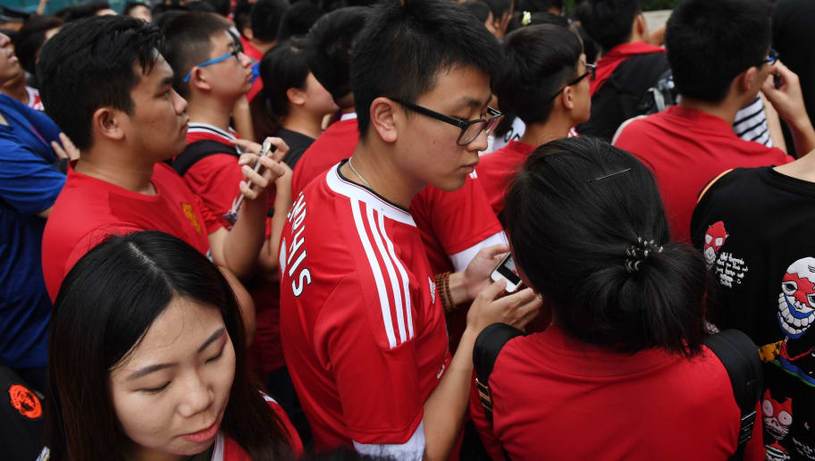 Fans of Manchester United wait outside the team's hotel after the match between Manchester United and Manchester City was canceled, in Beijing on July 25, 2016.   Fans gathered in the hope of seeing team members after the match was canceled because of extreme weather, which had made the pitch unsafe. / AFP / GREG BAKER        (Photo credit should read GREG BAKER/AFP/Getty Images)