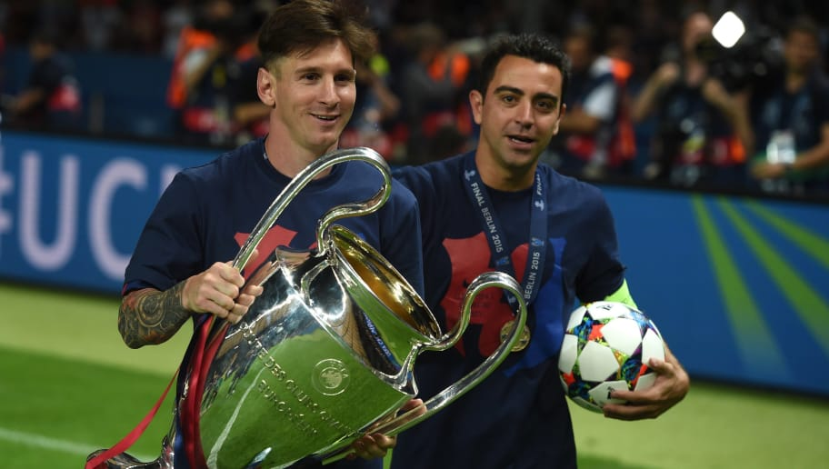 Barcelona's midfielder Xavi Hernandez (R) and Barcelona's Argentinian forward Lionel Messi celebrate with the trophy after the UEFA Champions League Final football match between Juventus and FC Barcelona at the Olympic Stadium in Berlin on June 6, 2015. FC Barcelona won the match 1-3.        AFP PHOTO / PATRIK STOLLARZ        (Photo credit should read PATRIK STOLLARZ/AFP/Getty Images)