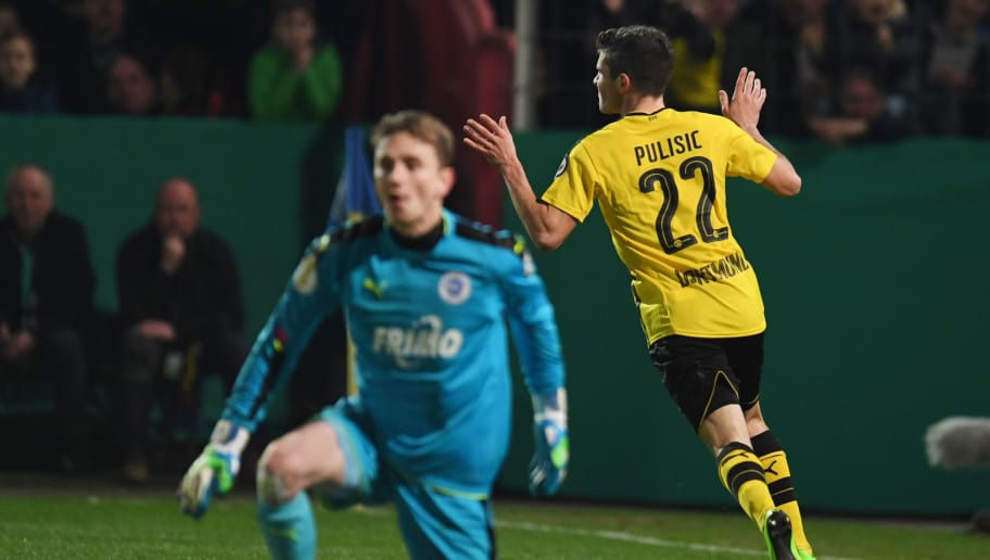 1779fe7c702 Dortmund s US midfielder Christian Pulisic (R) celebrates scoring the  opening goal during the German