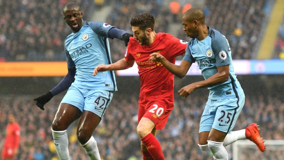MANCHESTER, ENGLAND - MARCH 19: Yaya Toure of Manchester City (L) and Fernandinho of Manchester City (R) battle for possession with Adam Lallana of Liverpool (C) during the Premier League match between Manchester City and Liverpool at Etihad Stadium on March 19, 2017 in Manchester, England.  (Photo by Michael Regan/Getty Images)